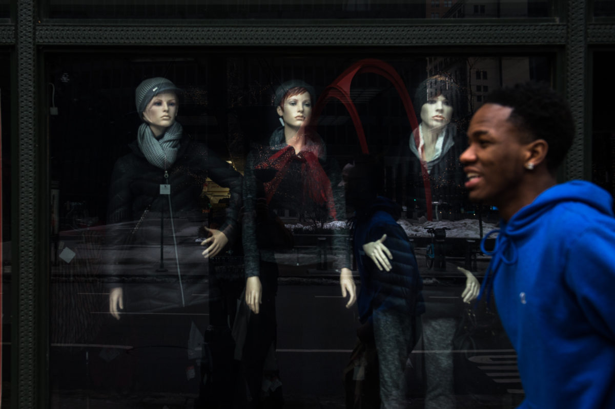 Manequins peer out of a downtown chicago store front.